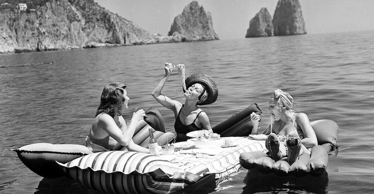 Unsettled life in Europe failed to change the slow pace of life on the Isle of Capri, off Naples, Italy. Some of the socialites who have come there to relax enjoy an aquatic luncheon serviced in the cool Mediterranean, Sept. 1, 1939. Swimming waiters push out the floating tables bearing meals which include wine and spaghetti. In the background are the rocks of Faraglioni. (AP Photo/Hamilton Wright)